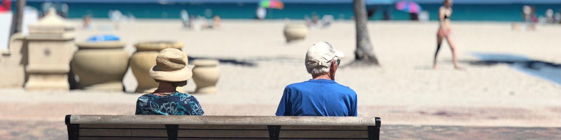 Ouder stel zit op bank bij het strand als illustratie bij uitruil partnerpensioen