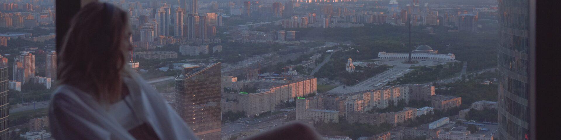 vrouw kijkt uit raam over stad, illustratie bij artikel over hypotheek